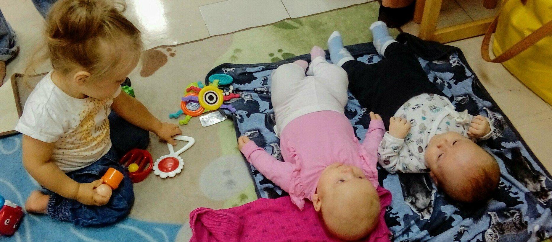 Pieniä perhekeholaisia, joista kaksi vauvaa makoilee lattialla ja yksi leikki-ikäinen istuu lelujen kanssa puuhaillen.